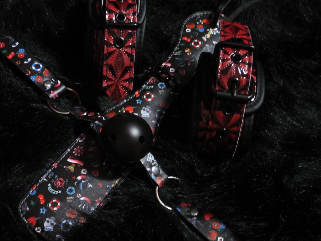 The ball gag & matching paddle, along with some unrelated red & black cuffs, on a black fur background.